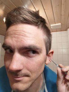 Foto von einem Mann welcher sich die Ohren putzt. Alternative Wattestäbchen aus stabilen Metal.